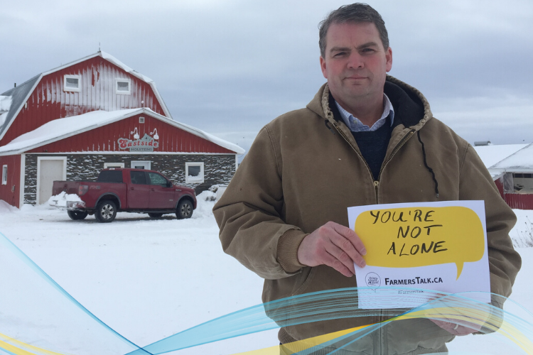 "Image of Minister Bloyce Thompson in front of his barn holding a FarmersTalk promo that reads ""You are Not Alone"""