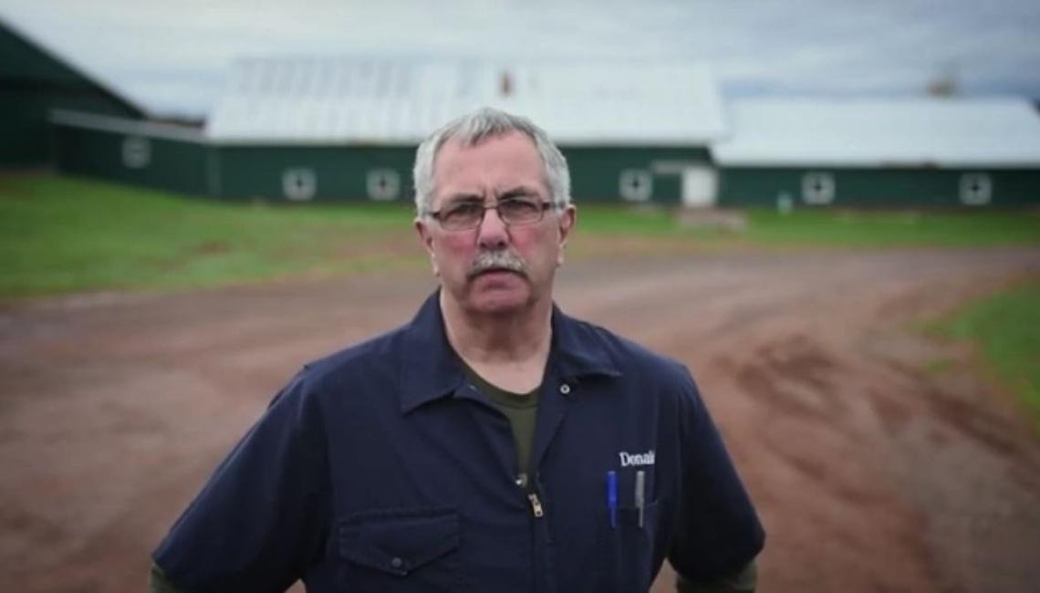 Image of farmer Donald in front of barns